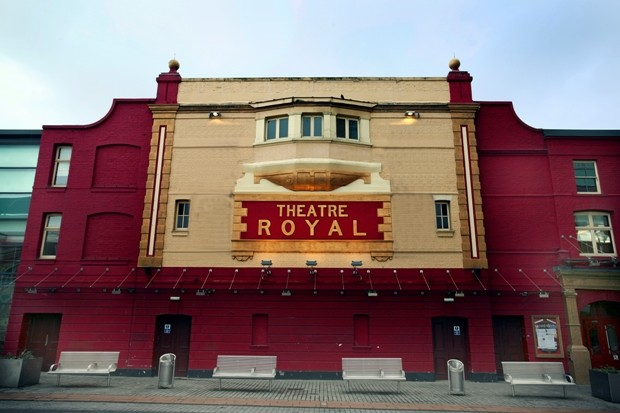 Photograph looking up at the exterior of the Theatre Royal in Stratford East, the building is red with cream embelllishment