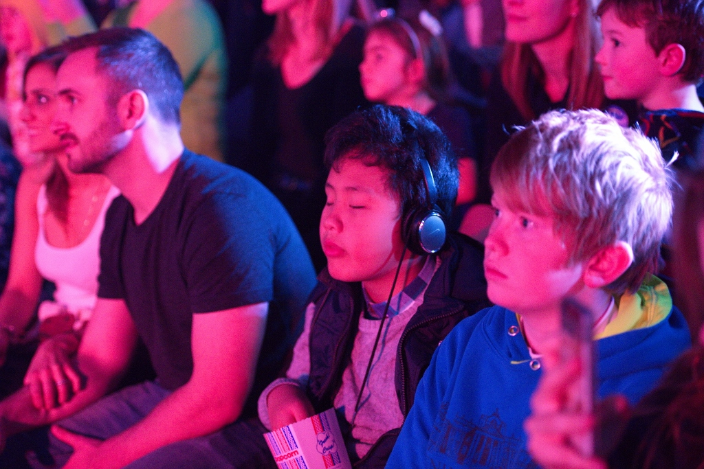 Boy among audience wearing headphones