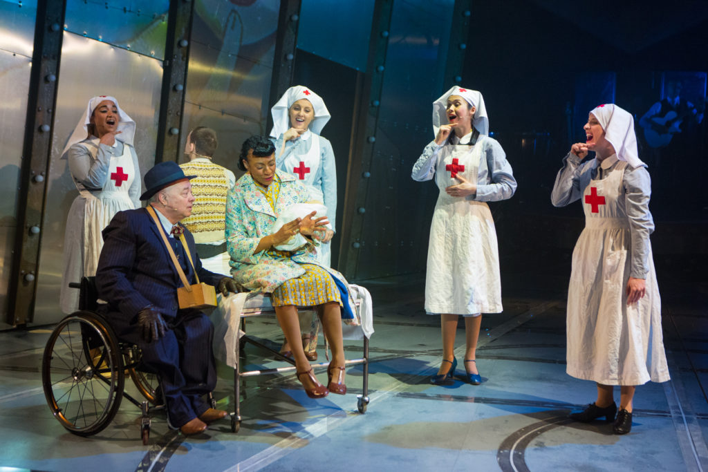 3 characters seated in hospital scene. 4 nurses sing and sign.
