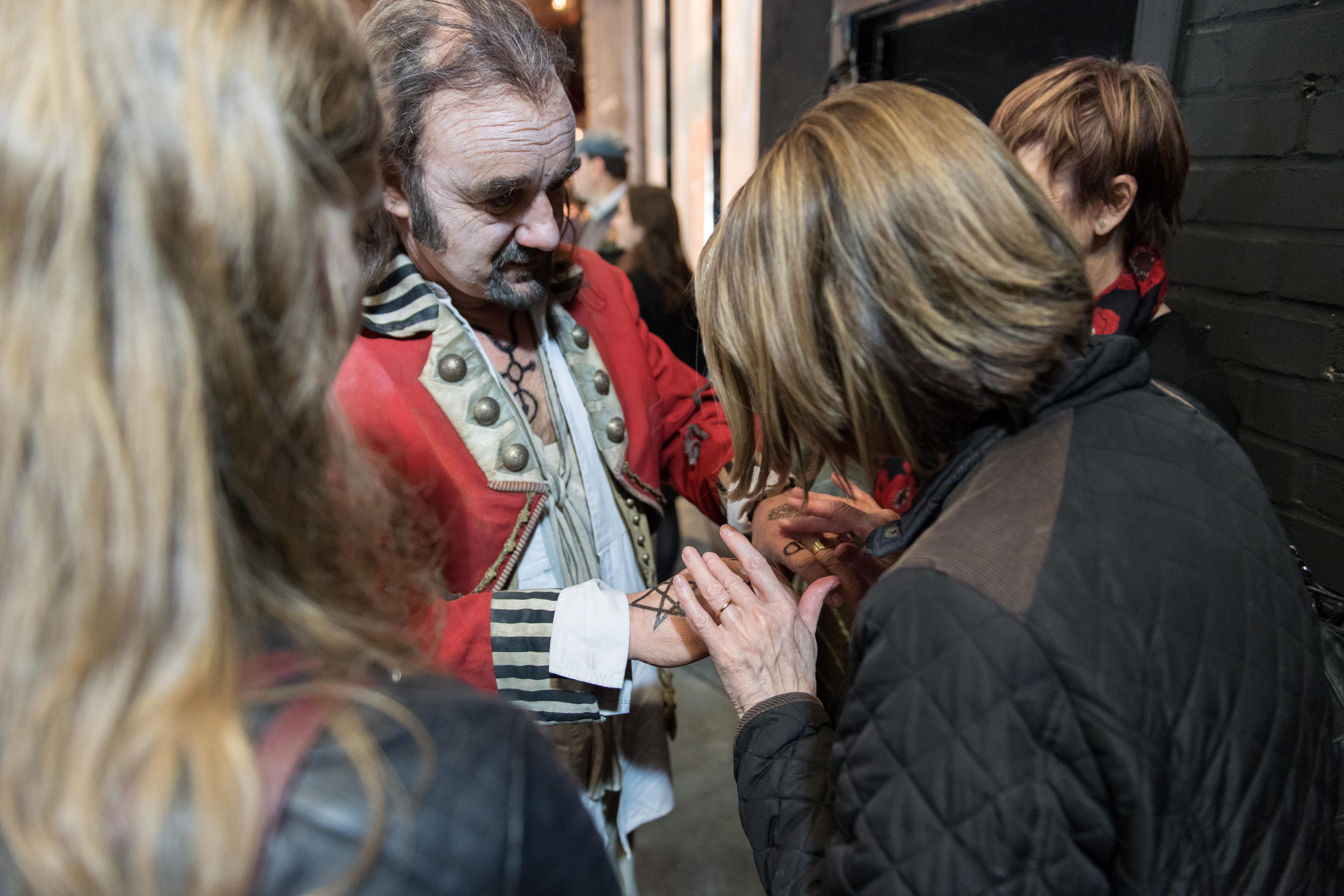 Woman touches the backs of the hands of a costumed actor