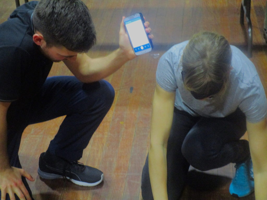 Two people crouched down - one holds out a phone, the other doing something on the floor outside the frame of the image