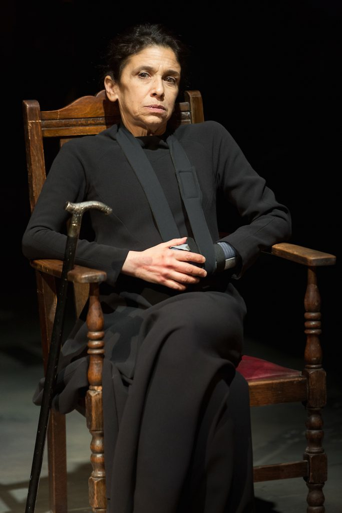 Woman wearing black seated in high-backed wooden chair.