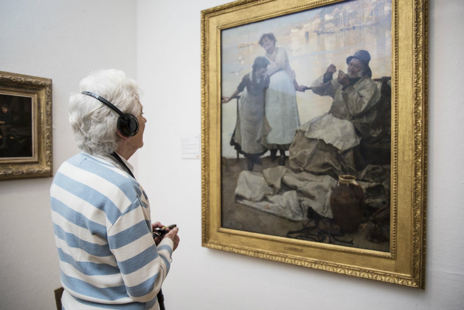 Grey-haired woman views painting, wearing headphones