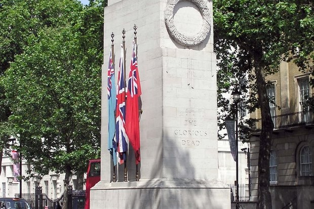 Photograph of the Cenotaph with flags in front and trees behind