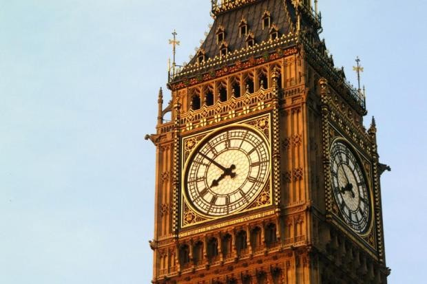 Photograph of the top of Elizabeth tower in the house of parliament showing the clock on two sides