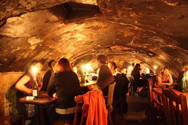 Interior of bar, a candlelit alley with several people drinking