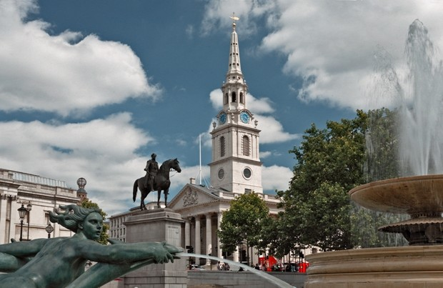Photogaph of white building, statur of a man on a horse outside and part of a fountain spraying water