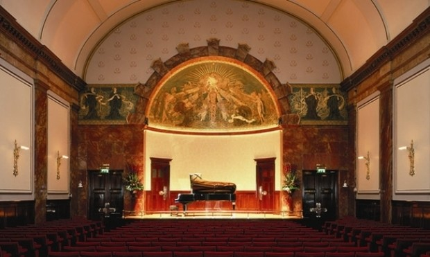 Interior shot of Wigmore Hall, showing empty chairs, a gold and red stage with a grand piano on it. An intricate dome is above the stage.