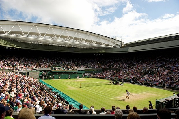 Photograph taken from the corner of tennis court with players on the grass and audience in the crowd