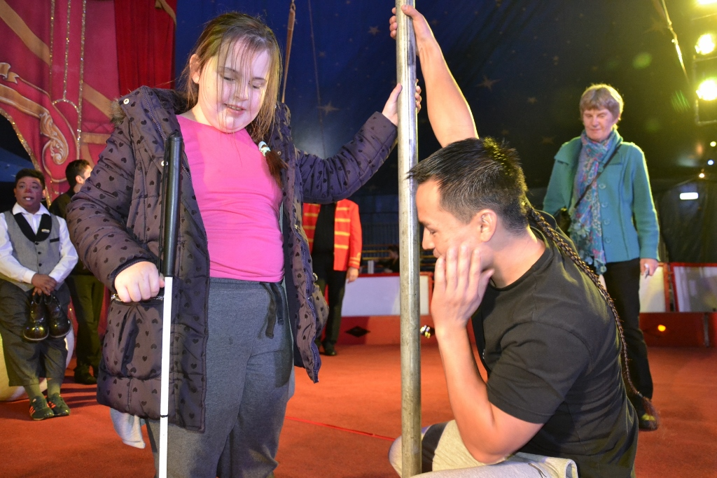 Performer shows girl the pole he will climb during the performance