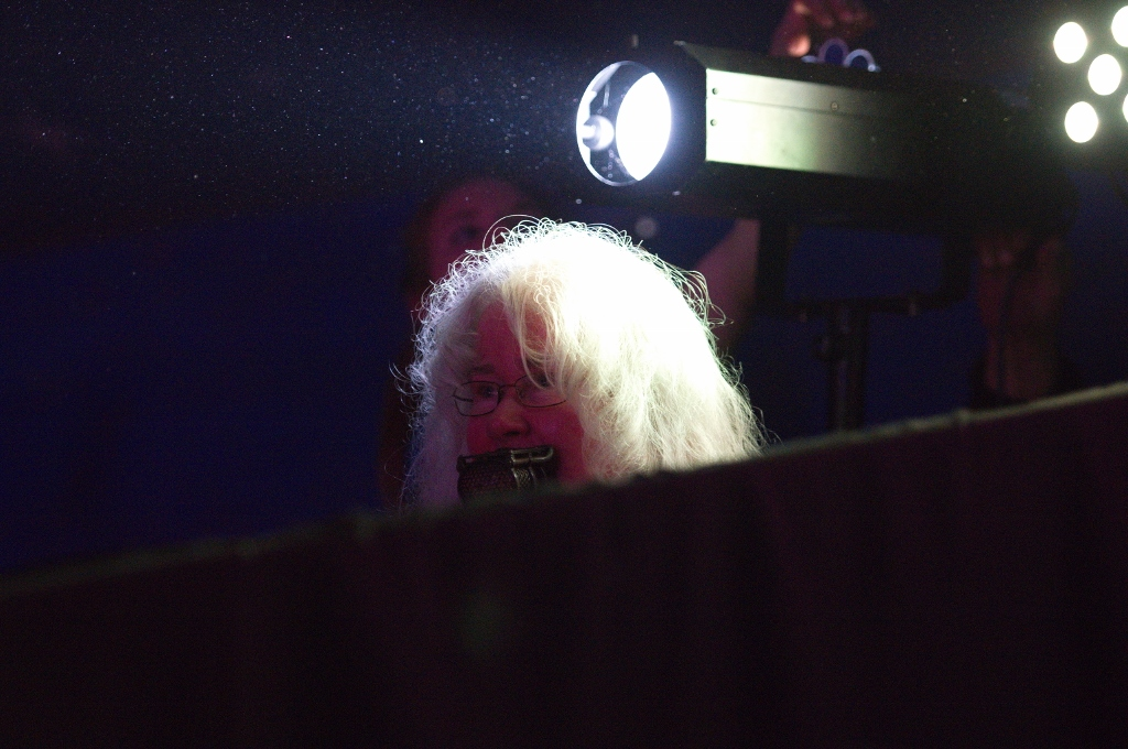 Seated woman in semi-darkness using lip microphone