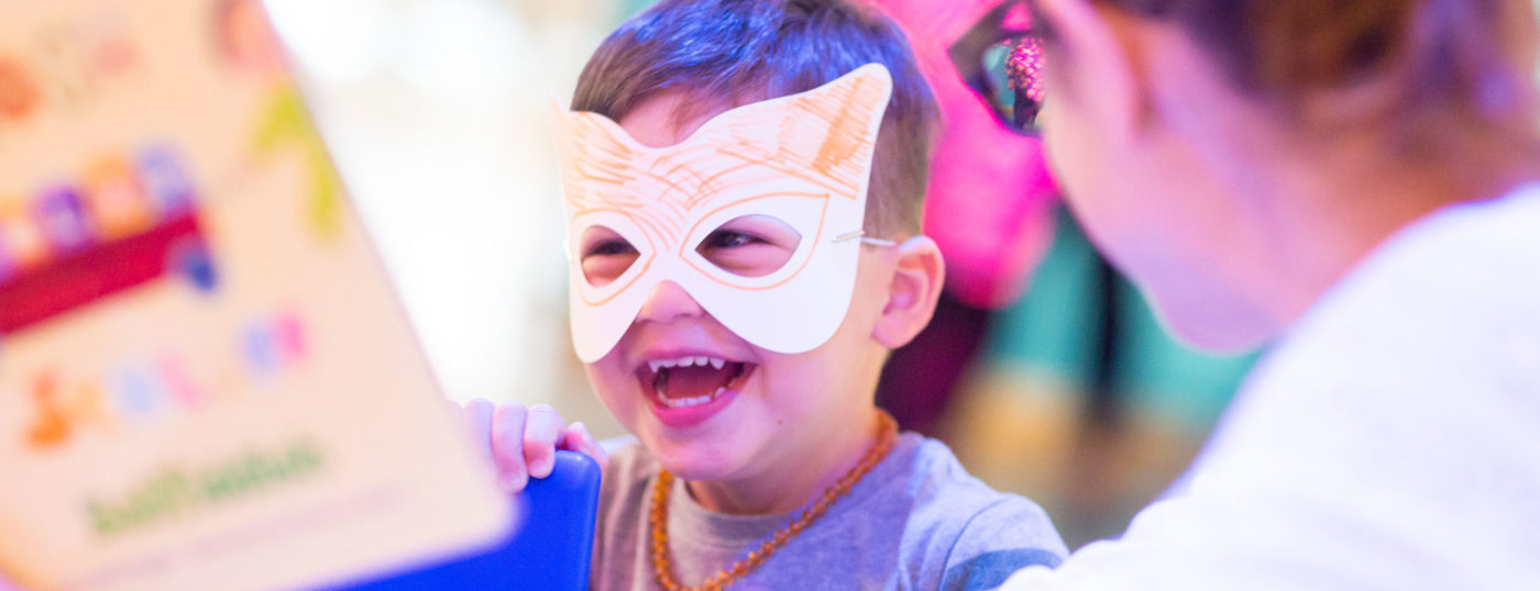 A smiling boy wearing a hand-decorated mask at The Jewish Museum