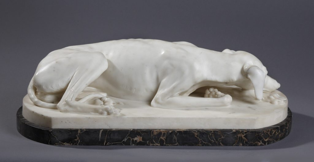 white stone sculpture of reclining greyhound