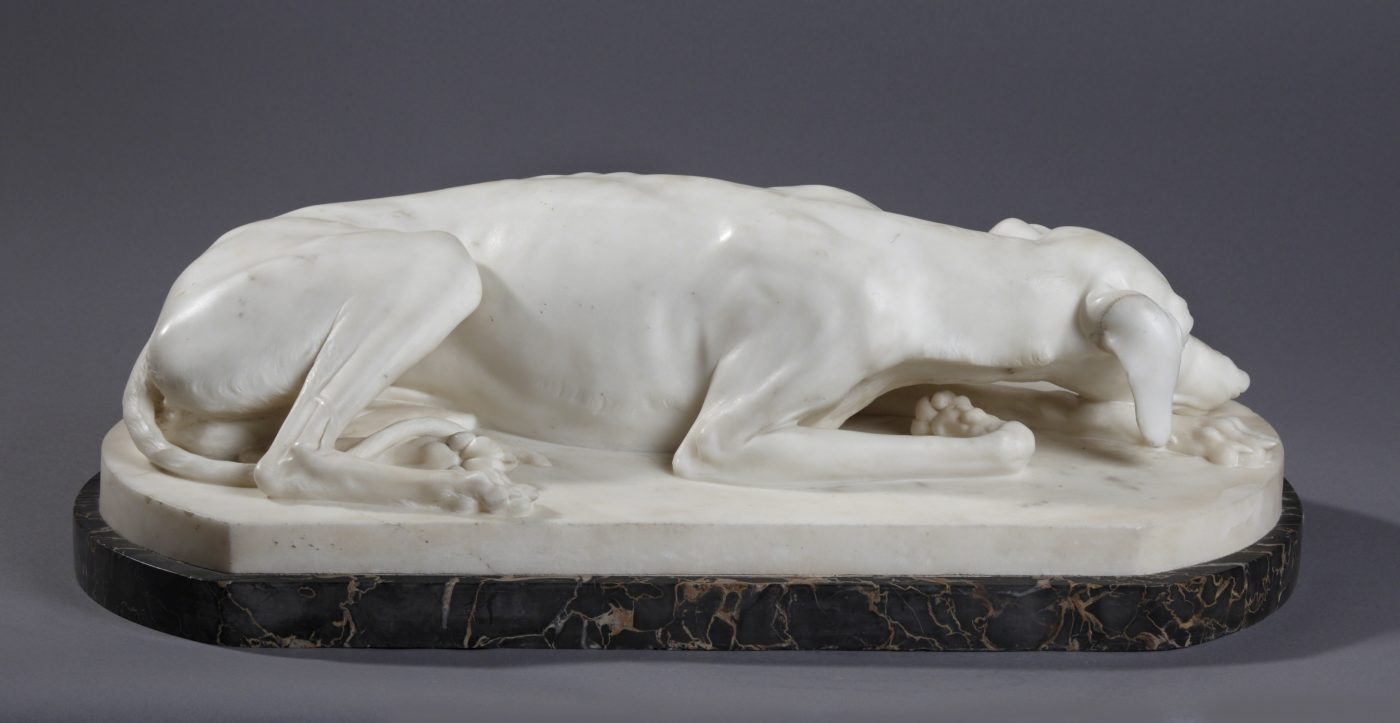 white stone sculpture of reclining greyhound