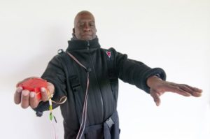 Man in boiler suit holds cube, arms stretched in front of himself
