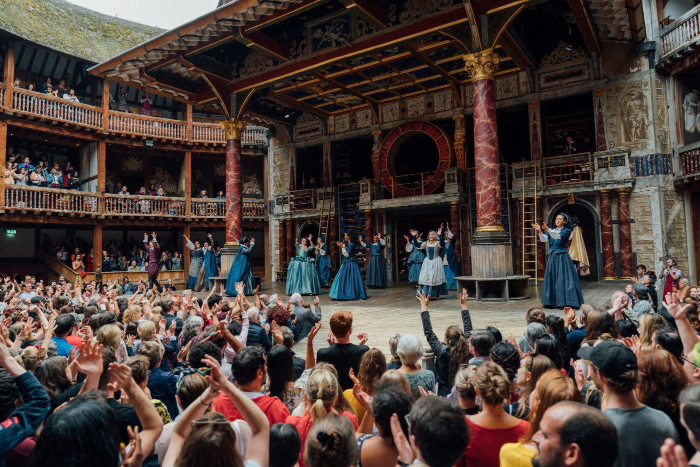 View of actors on Globe stage with audience standing
