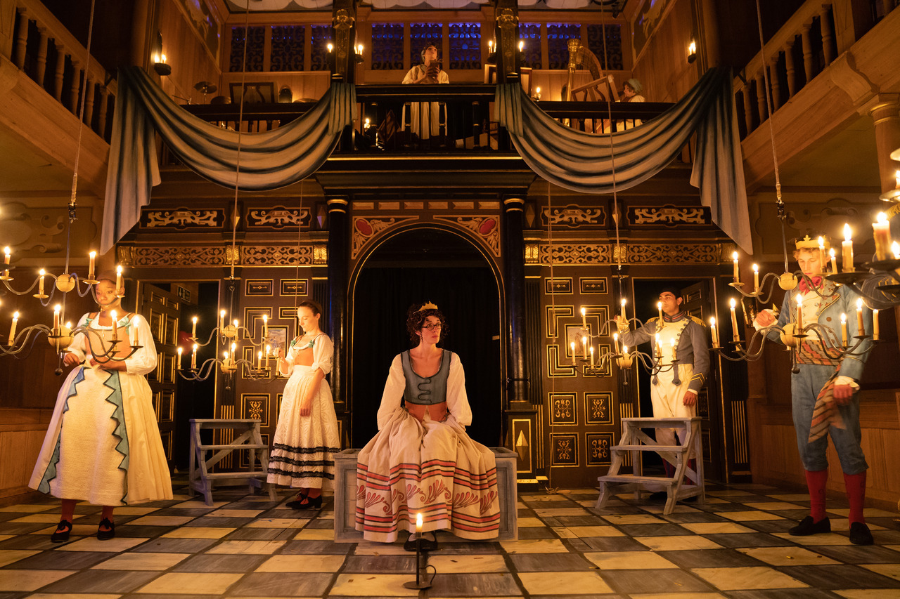 Actors in interior of Sam Wanamaker Playhouse lit by candles