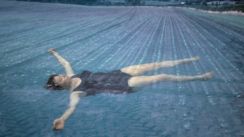 Colour photograph showing Jo Spence in a bathing suit, lightly floating under the surface of the water of a vast lake