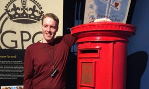 Glen Turner stands by a red pillar box