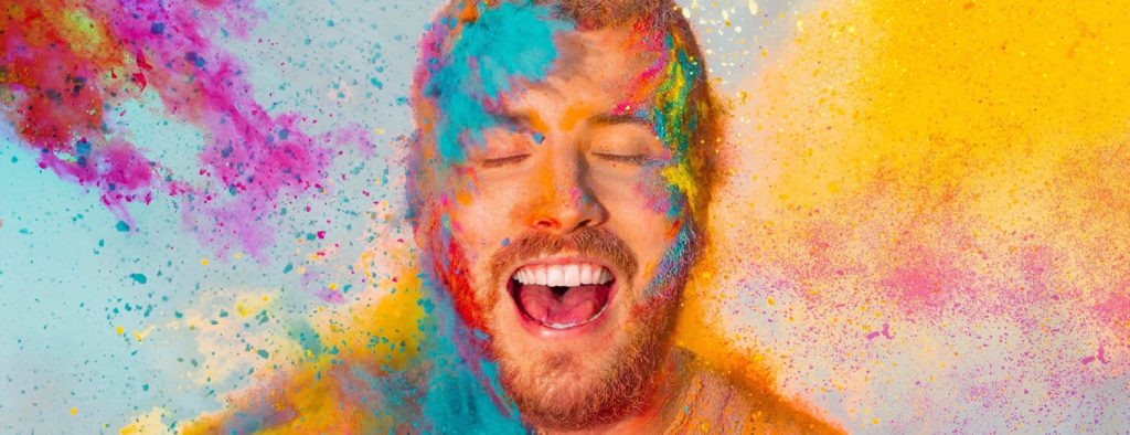 Powdered paint in vibrant colours hits the face of a young white man with open mouth and closed eyes. He has short red hair and beard and wears an orange t-shirt. Join Matt as he discovers Reasons To Stay Alive audio-described by VocalEyes - describing the arts at the Bristol Old Vic and touring this autumn; https://bit.ly/2YDAwPv