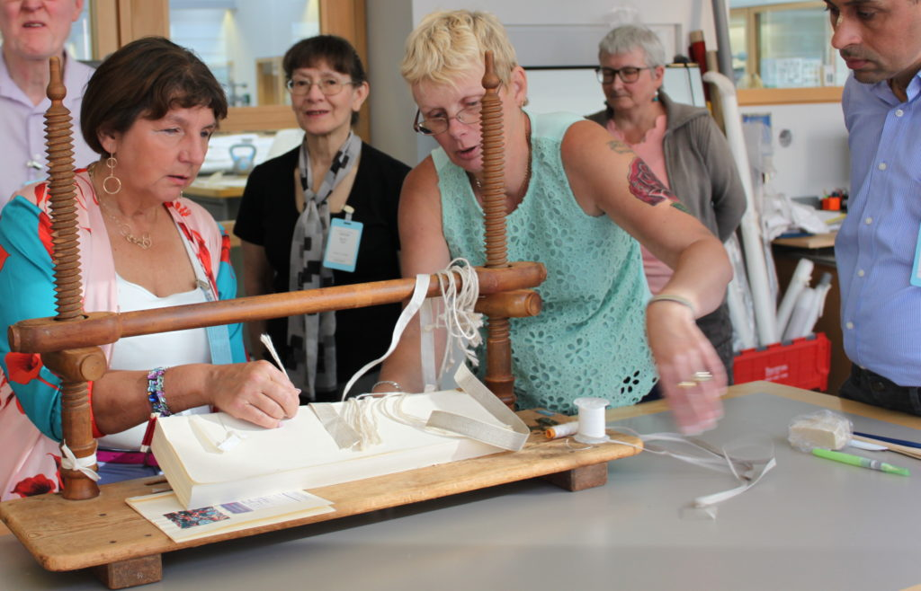 Attendees handle book binding techniques
