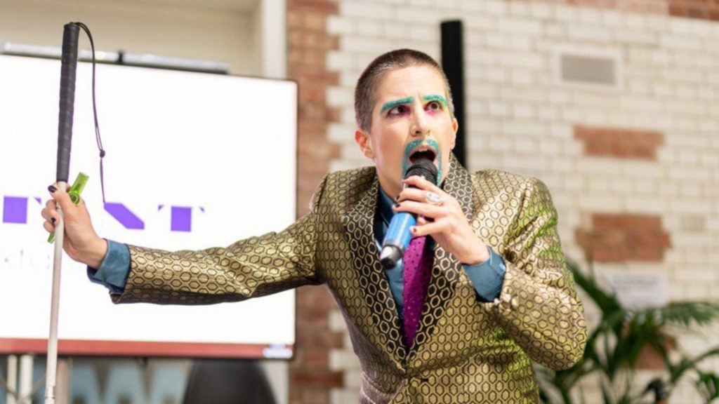 Queer blind theatre practitioner Amelia Cavallo AKA Tito Bone performing with a microphone and a white cane, wearing glittery make-up and beard in a gold suit
