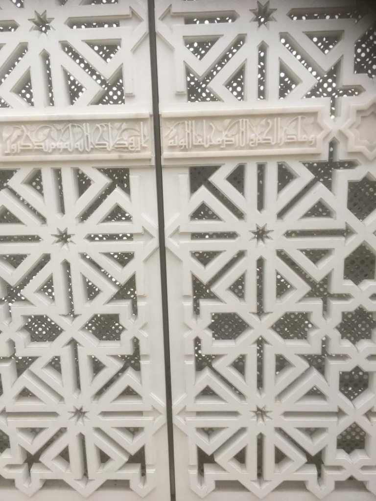 Carved white fretwork panel with Islamic script