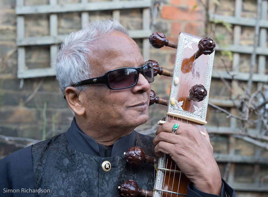 Internationally renowned sitar player Baluji Shrivastav OBE holds the neck of the sitar wearing a black suit and sunglasses.