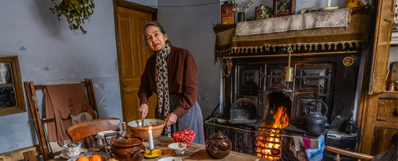 A woman stands at a wooden table stirring a mixing bowl, traditional Christmas foods are spread out before her and there is a large open fire in the range.