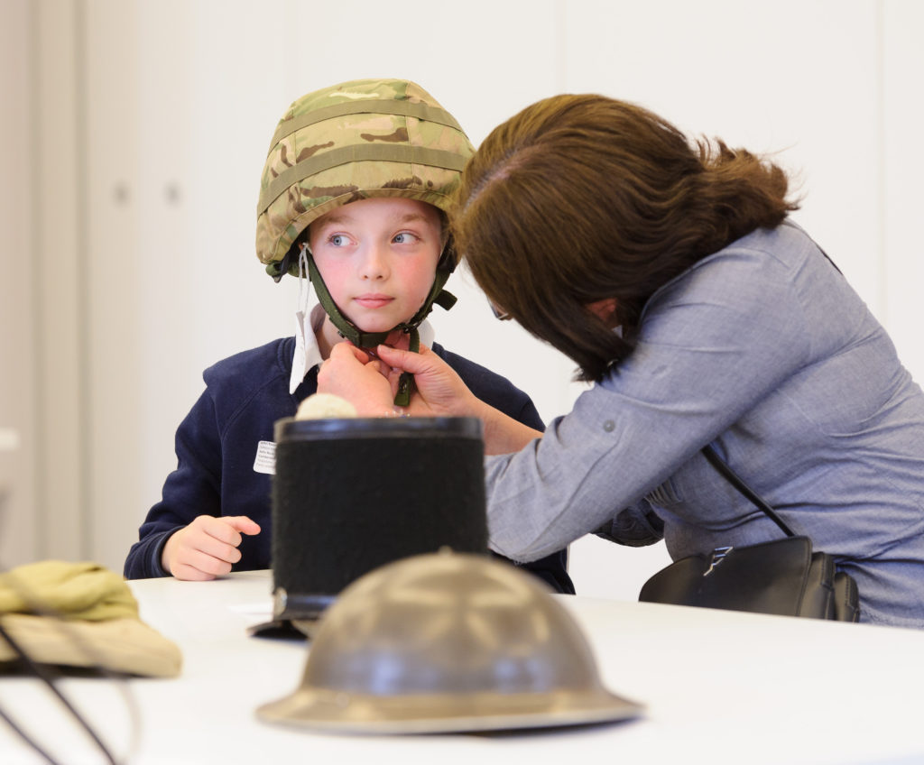 Someone helps a boy try on an army helmet, with some different army hats on the table in front of him