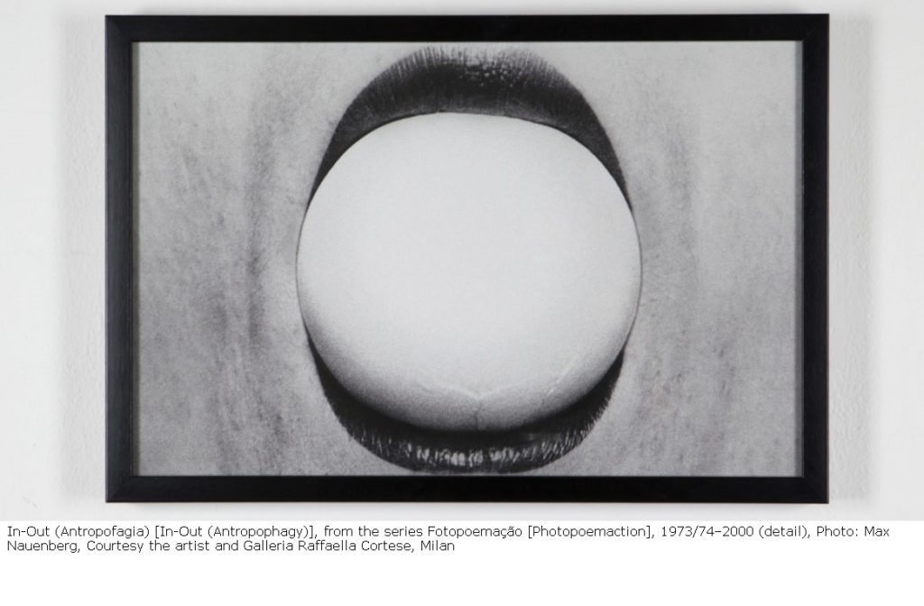 In-Out (Antropofagia) [In-Out (Antropophagy)], from the series Fotopoemação [Photopoemaction], 1973/74–2000 (detail), Photo: Max Nauenberg, Courtesy the artist and Galleria Raffaella Cortese, Milan. Black and white close-up photograph of a woman's lips holding a white ball.
