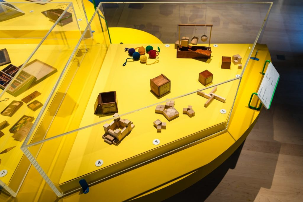 Fröbel's Gifts. Photograph of an exhibition display case with a bright yellow base. Inside the case are several small wooden toys in various shapes and 6 balls of coloured wool.