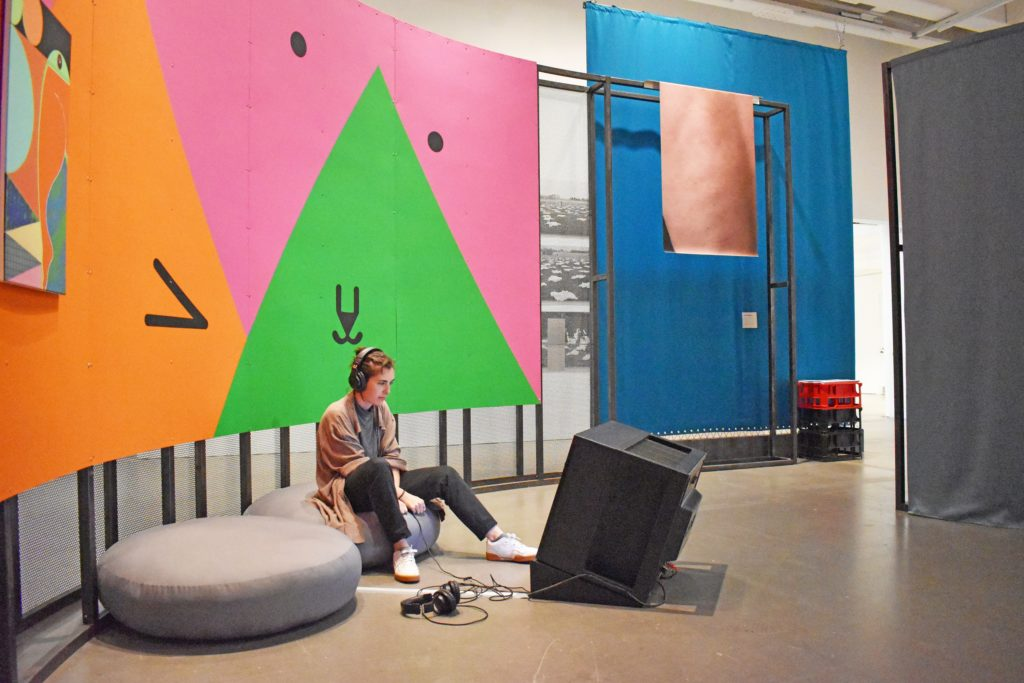 [Image: Still I Rise. View of the gallery, on the wall is Ad Minoliti's 'Triangles Watching Playlist' a brightly coloured wall painting, on the floor a person wearing headphones is sitting on some cushions watching a TV playing videos selected by the artist from YouTube.]