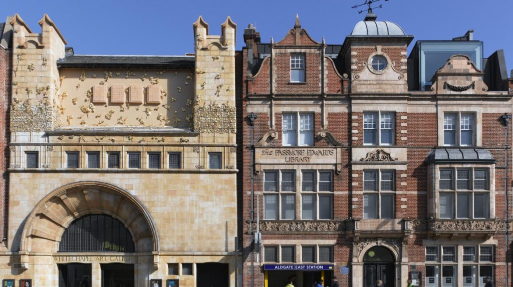 The  facade of the Whitechapel Gallery; To the left of the building is the gallery entrance, and to the right, the Passmore Edwards Library Entrance. The left of the building is a light, sand coloured stone, and features Rachel Whiteread's permanent commission 'Tree of Life' which consists of four stone window casts as well as clusters of leaves, cast in bronze and plated in gold leaf, emblazoning the gallery's facade with shimmering foliage. The right library side of the building is red brick, and stands above the Aldgate East underground station entrance.