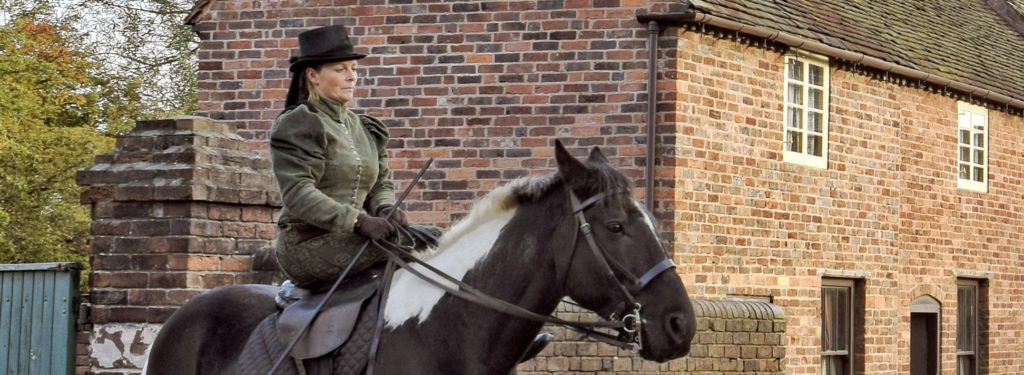 Danny, a large a brown and white horse, stands by a brick house. He is being ridden side-saddle by a woman in dark green Victorian costume.