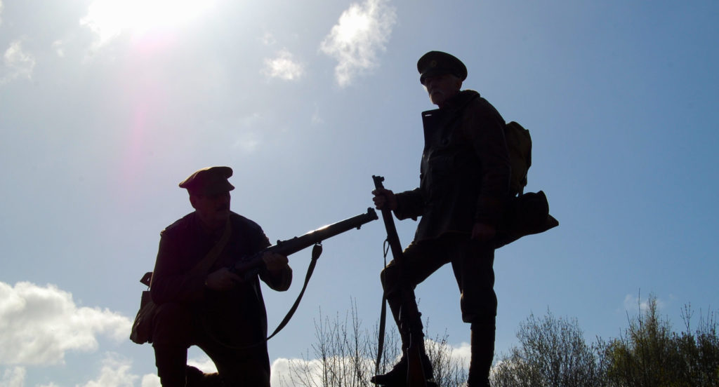 Silhouette of two soldiers against a sunny sky one standing one kneeling