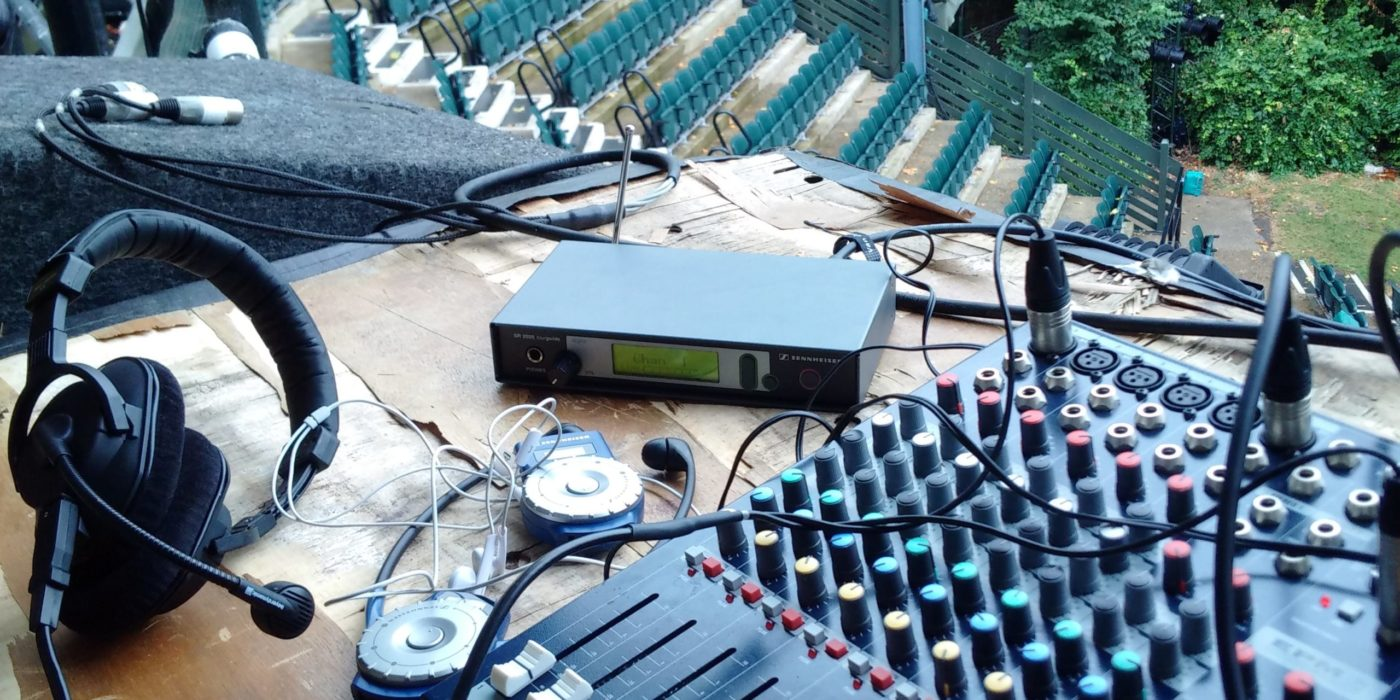 The image shows the describer position in an outdoors theatre. There's a table with sound equipment, a pair of headphones with a microphone and two audio description headsets. From there, the describer has a direct line of sight to the stage and the seats, the later of which are visible in the background of this image.