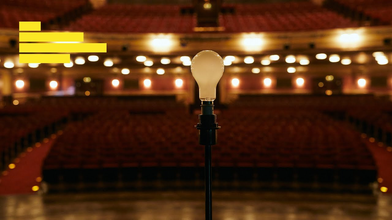 Light bulb (off) silhouetted against empty theatre auditorium