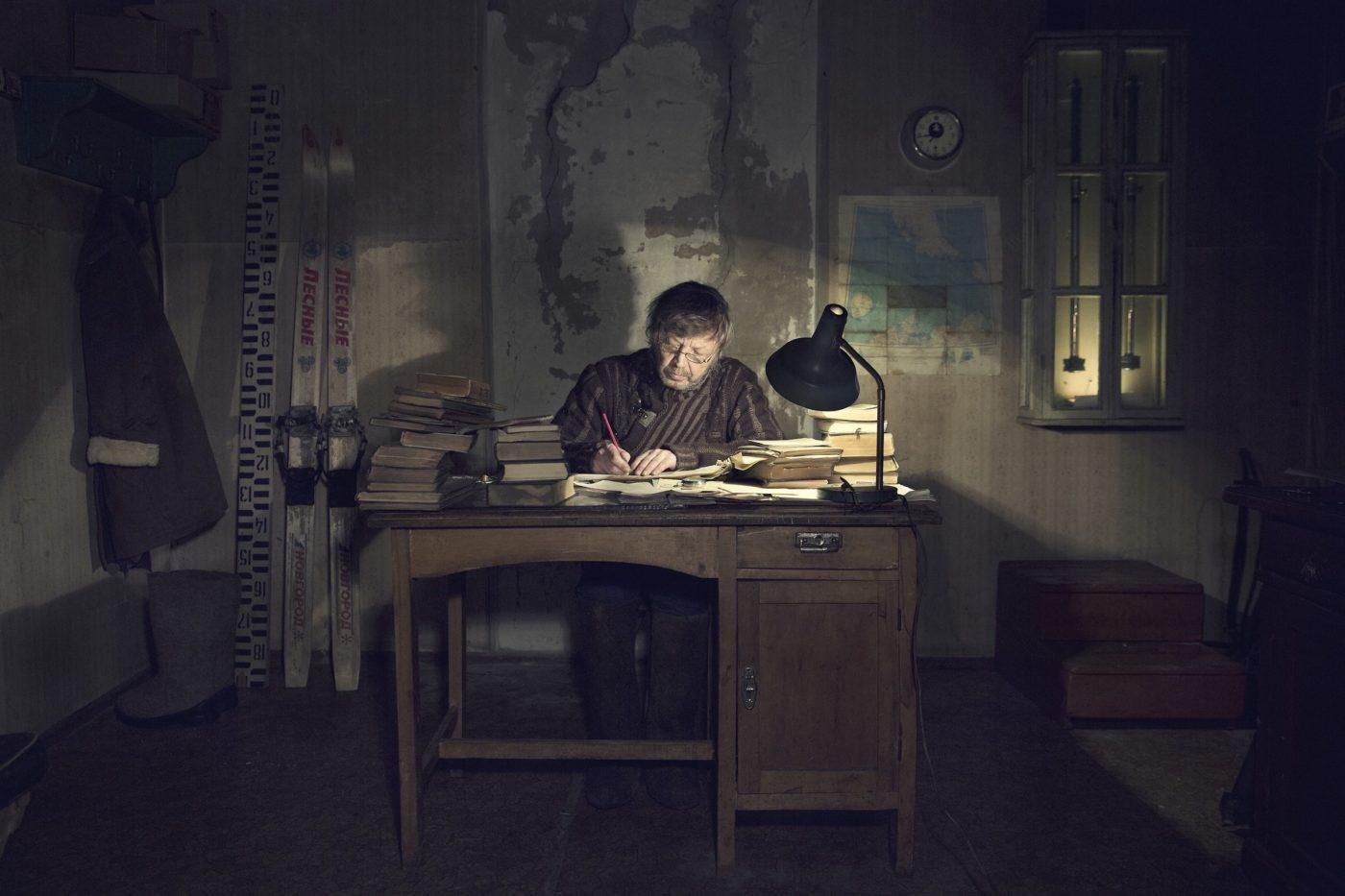 Man writing at desk, illuminated by desk lamp