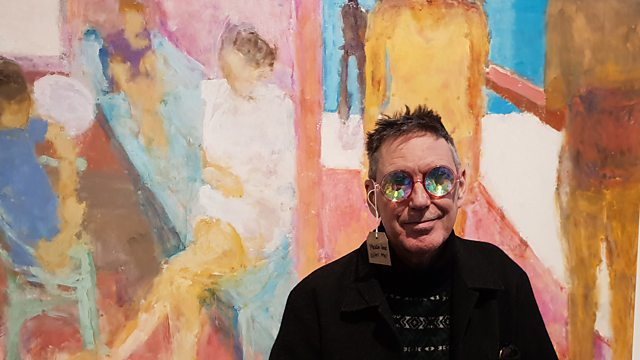Richard Butchins stands in front of a large colourful painting