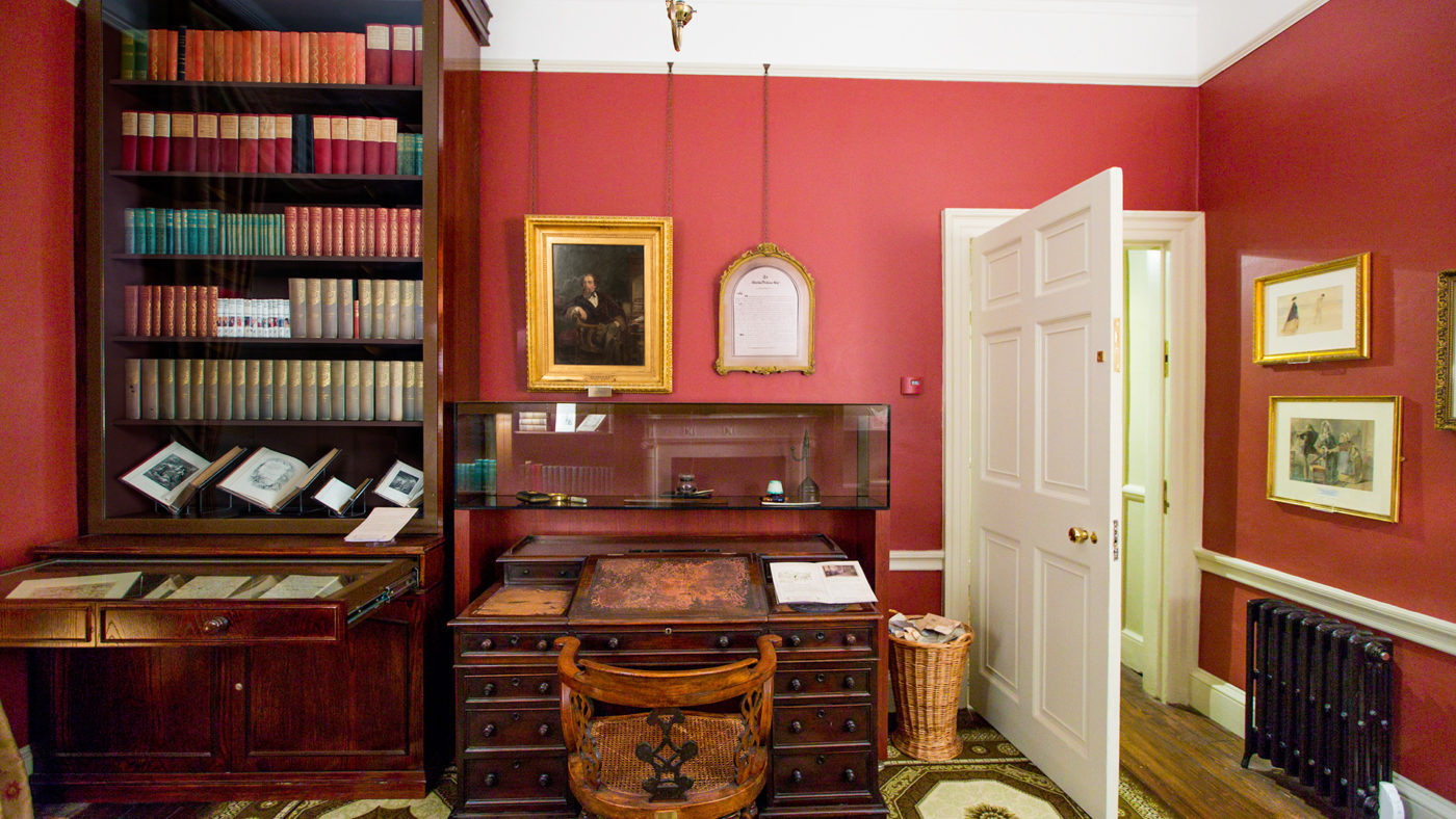 Study in Charles Dickens Museum with large Victorian wooden writing desk against red wall