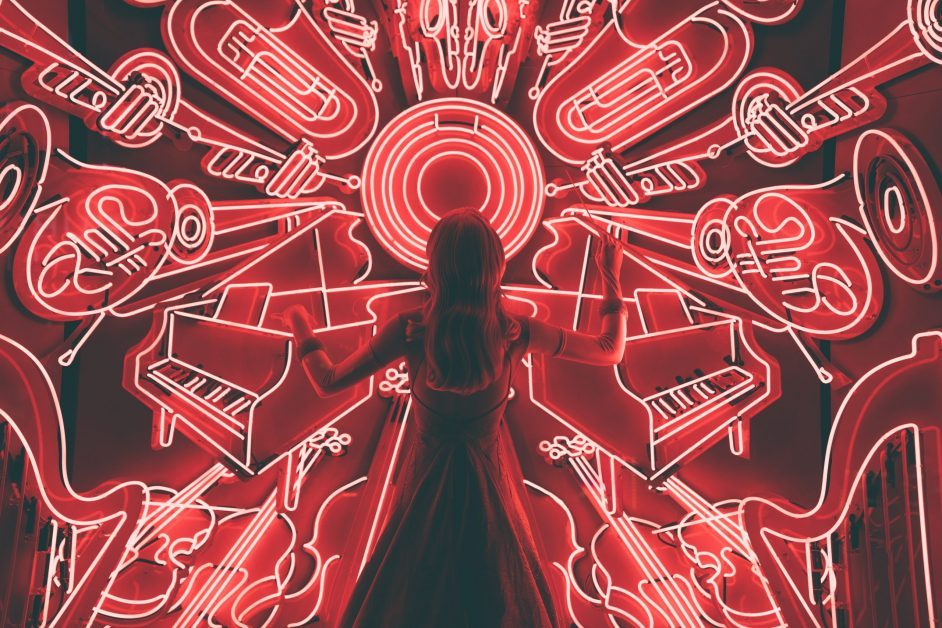 young girl stands in front of illuminated outlines of musical instruments