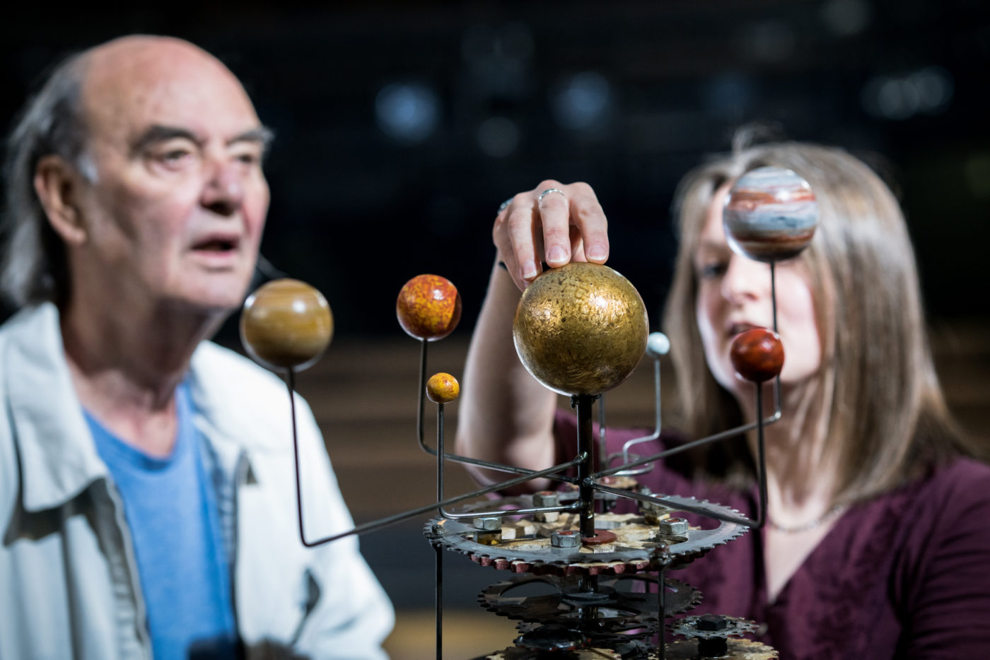 A man and a woman explore a model of the solar system, approximately 50 cm tall: a golden sphere in the centre represents the sun, with smaller spheres representing planets surrounding it. The planets are supported on wires, at varying distances from the sun, and all are connected to a system of cogs at the base that allow the planets to circle round the sun.