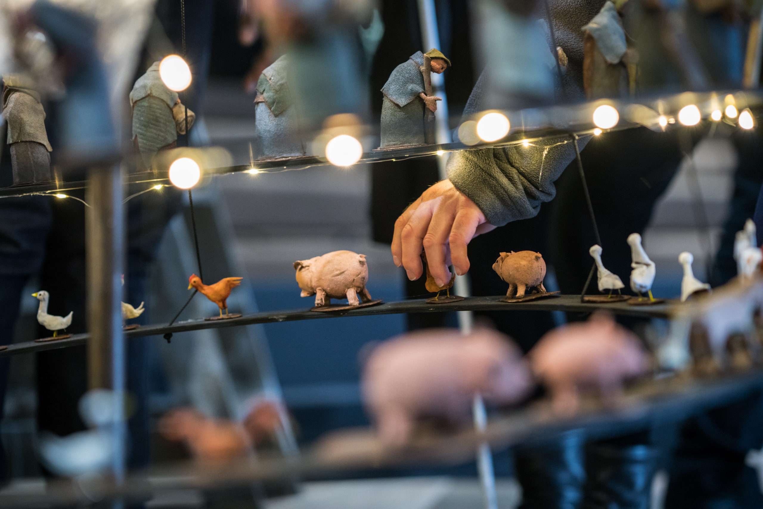 A close up shows two narrow ring-shaped shelves of miniature figures with a hand reaching down to touch one of them. One shelf holds animals: chickens, geese and pigs. The shelf above holds medieval peasants in dull blue and grey clothes, hunched over, some leaning on sticks. Fairy lights run round the shelves.