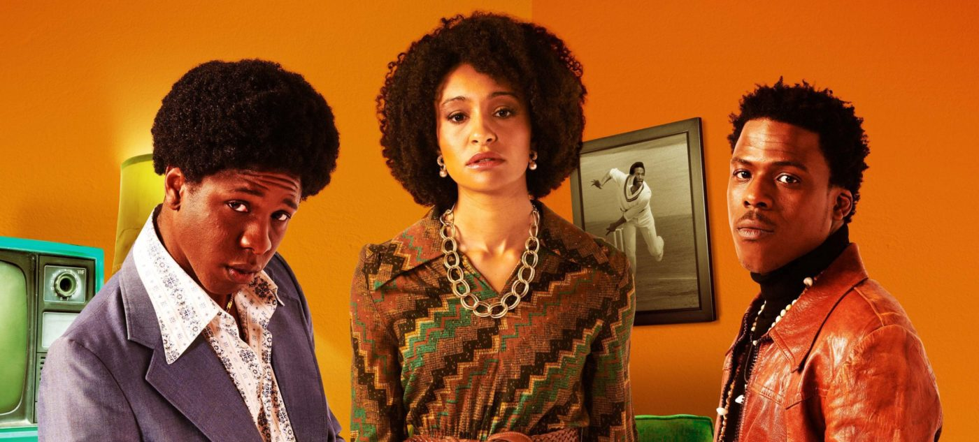 Actors Nickcolia King-N'da, Natalie Simpson and Toyin Omari-Kinch dressed in costume and looking towards the viewer in a room with burnt orange walls and a picture of a cricketer bowling hanging behind them.