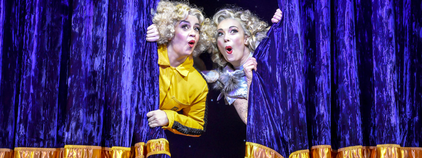 Image shows two Mischief actors leaning out from behind a partially opened blue and gold theatre curtain. They hold the curtain tight and their faces express surprise and delight.