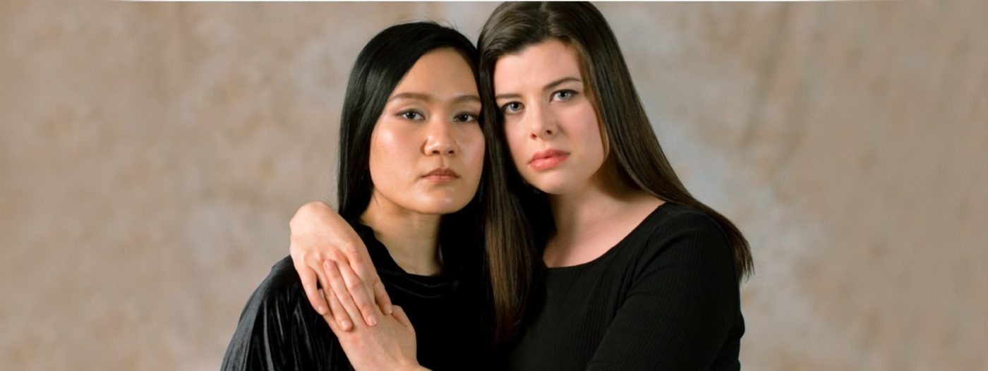 Image shows Jonadette Carpio and Stephanie Wake-Edwards as the two sides of Anna in The Seven Deadly Sins. Both women are dressed in black and looking directly looking at the camera with sombre expressions