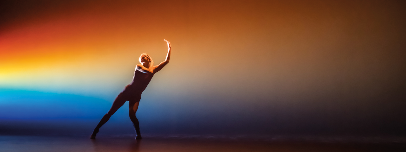 A solo dancer seen at a distance, against a background of prismatic light. With feet planted wide apart, the dancer leans at a steep angle, one knee bent, looking up , shielding their face from the light.