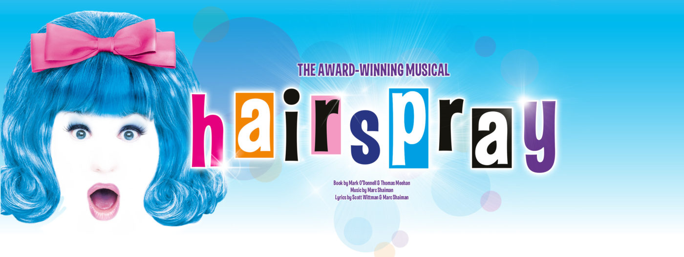 The left third of the image is filled with a close-up on Tracy Turnblad's face, mouth and eyes wide open, a large peach coloured bow in her dark bobbed hair and a completely white face, the only contrast indicating her nose. The background is light blue, there are multicoloured pastel circles around the text: The Award Winning Musical, hairspray, book by Mark O'Donnell and Thomas Meehan, music by Marc Shaiman, Lyrics by Scott Whitman and Marc Shaiman.