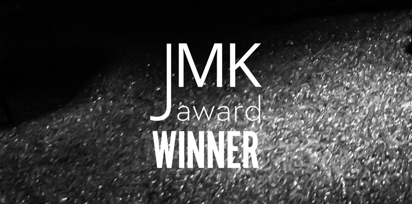 "A black background with shiny particles. The text ""JMK award winner"" is superimposed in the middle of the image."
